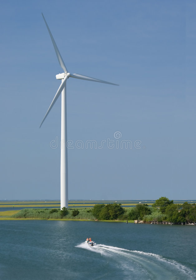 Windmill and boat. Boat cruises by modern windmill. Atlantic City wind farm royalty free stock photos