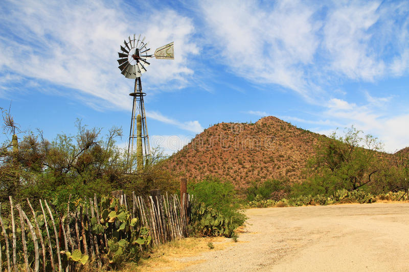 Windmill and Butterfly Garden on La Posta Quemada Ranch in Colossal Cave Mountain Park. Windmill, mountain and butterfly garden along a fence on the La Posta royalty free stock photography