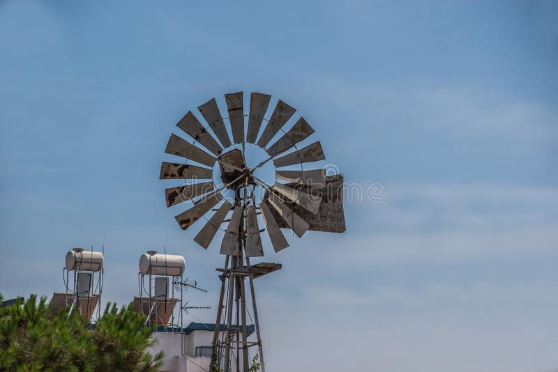 Windmill in a city environment with blue sky royalty free stock photography