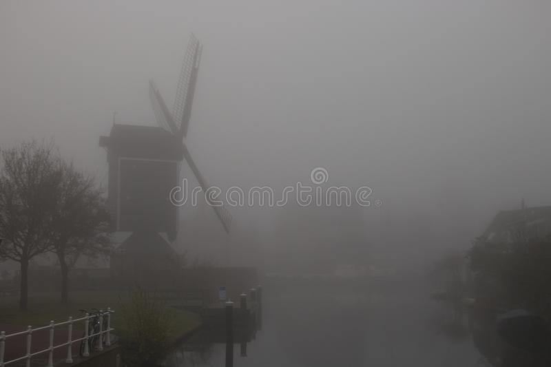 Windmill in dense fog stock images