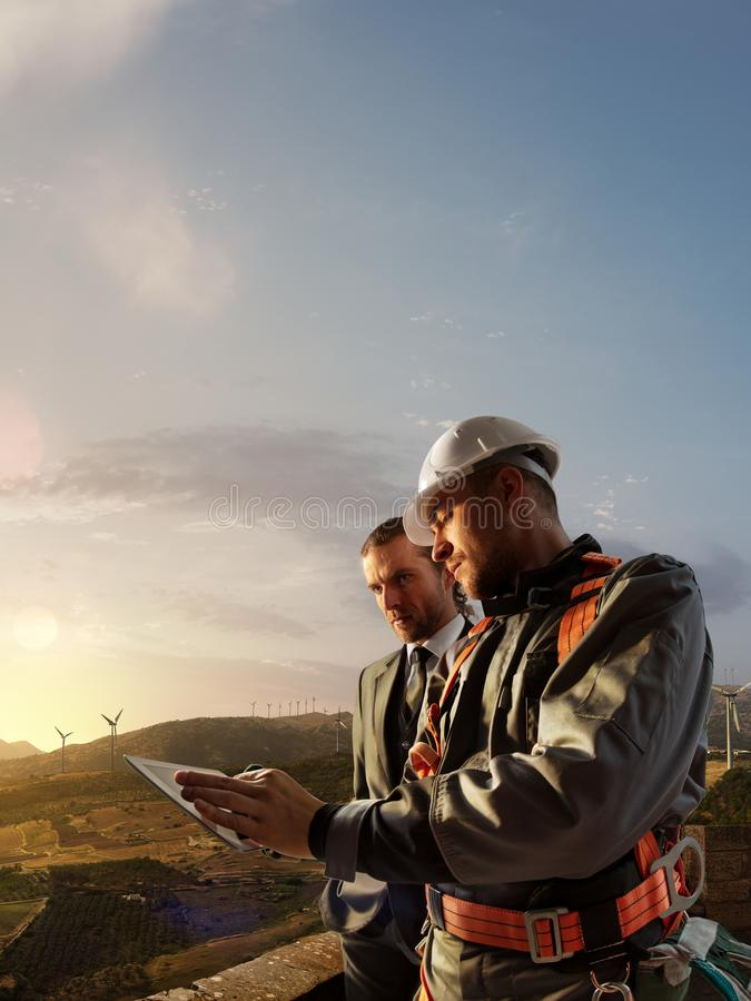 Windmill engineer and businessman planing new ecology project. they standing and looking in tablet. Around wind generators royalty free stock photos