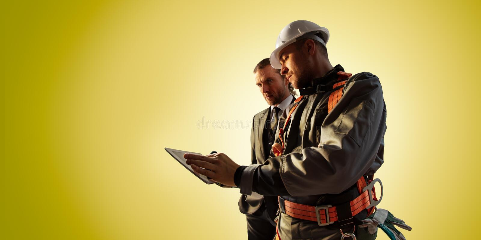 Windmill engineer and businessman planing new ecology project. they standing and looking in tablet. Color studio background stock images