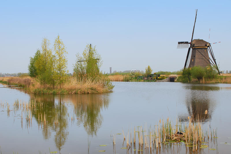A windmill facing a house and an island of trees with a bird nest on the foreground bottom right corner stock photos