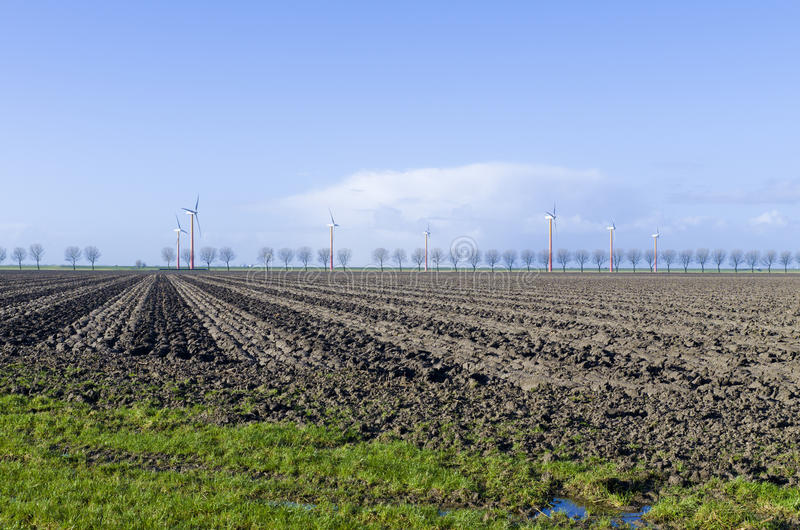 Windmill farm in Almere, Netherlands. Plowed field with a windmill farm in the background in Almere, Netherlands stock photos