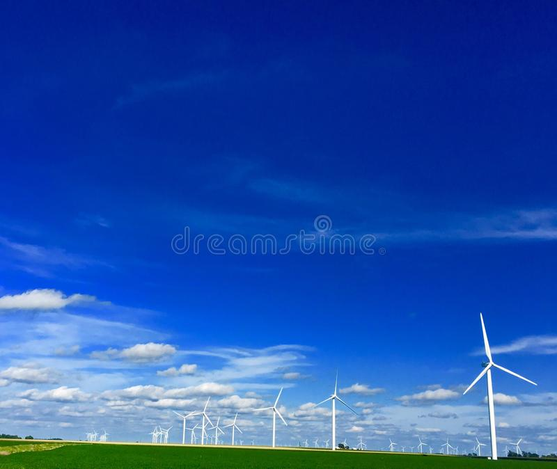 Windmill Farm. Windmills stretching out over farm fields royalty free stock images
