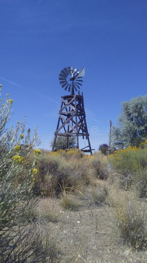 Windmill in a field of sagebrush. Windmill in a field of s. it's a   day. , , , copy, space, , , , , , yellow, colors, sunlight, , , eastern, oregon stock images