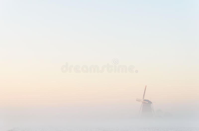 Windmill in the fog stock photos