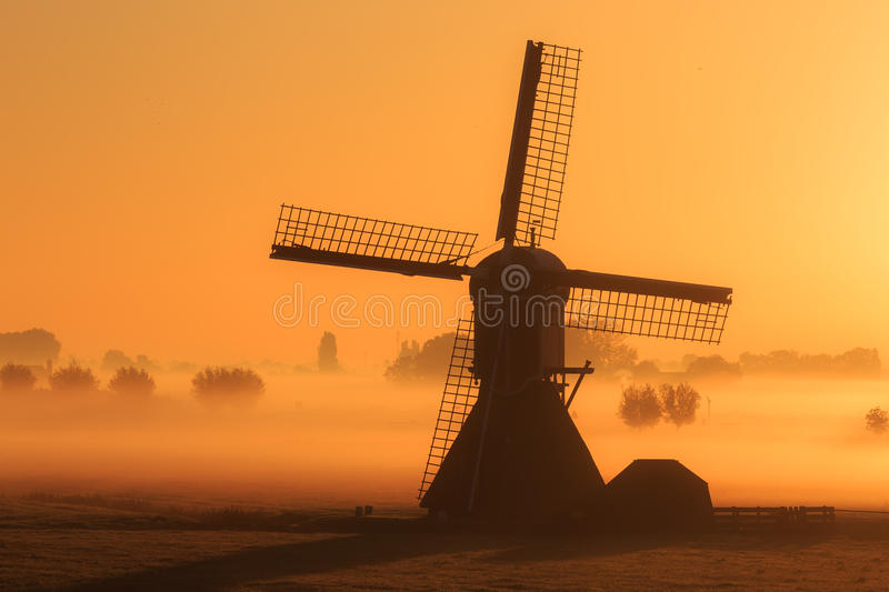Windmill foggy morning. Beautiful silhouette of a traditional windmill on a foggy morning in the Netherlands stock image