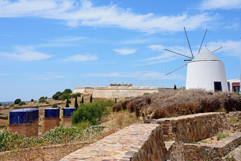 Windmill and fort, Castro Marim. Whitewashed traditional windmill at the top of the hill by the fort, Castro Marim, Algarve, Portugal, Europe royalty free stock image