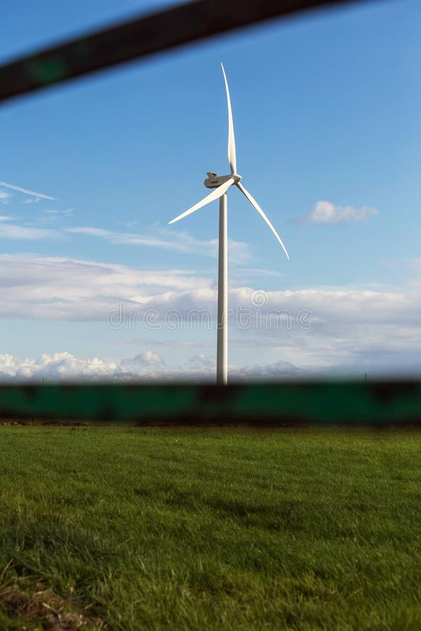 Windmill with fresh green grass and clear blue sky in summer, energy concept near fence royalty free stock image