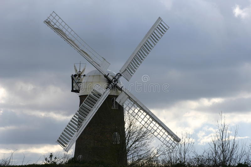 Windmill. From the front showing the cap and all four sails with a background of blue and grey sky with white clouds stock photography