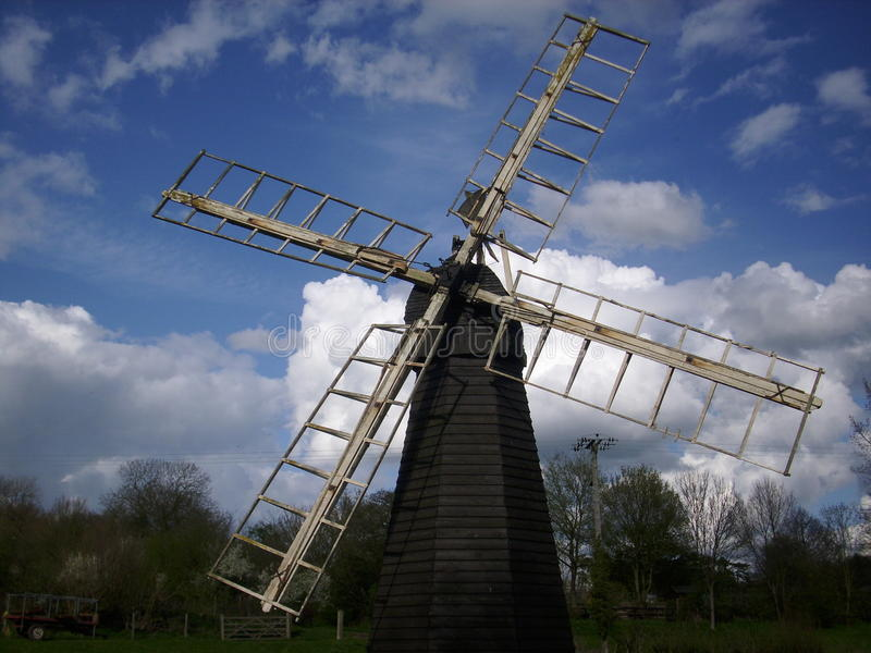 Windmill from the front. Showing the cap and all four sails with a background of blue and grey sky with white clouds and trees stock image