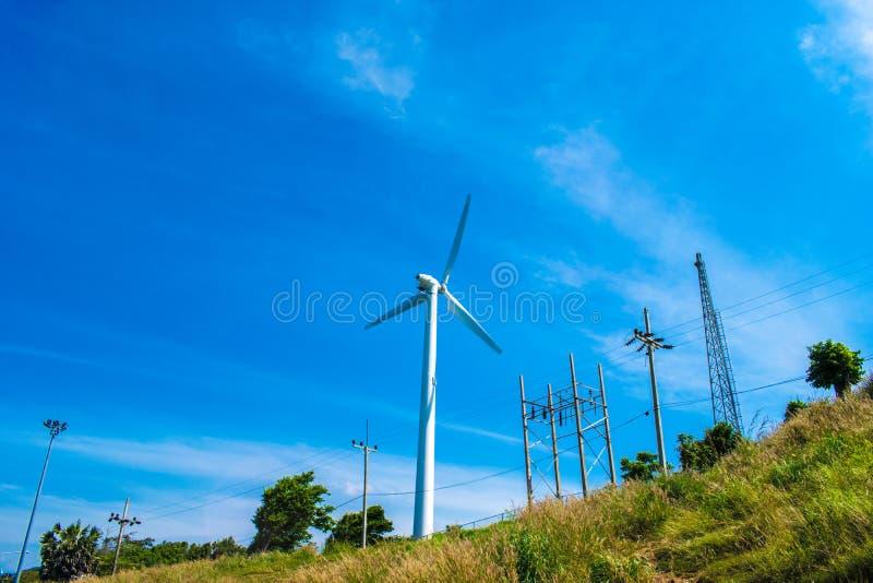 Windmill generator in wide yard / Yard of windmill power generatorunder blue sky, shown as energy industry concept. royalty free stock photos
