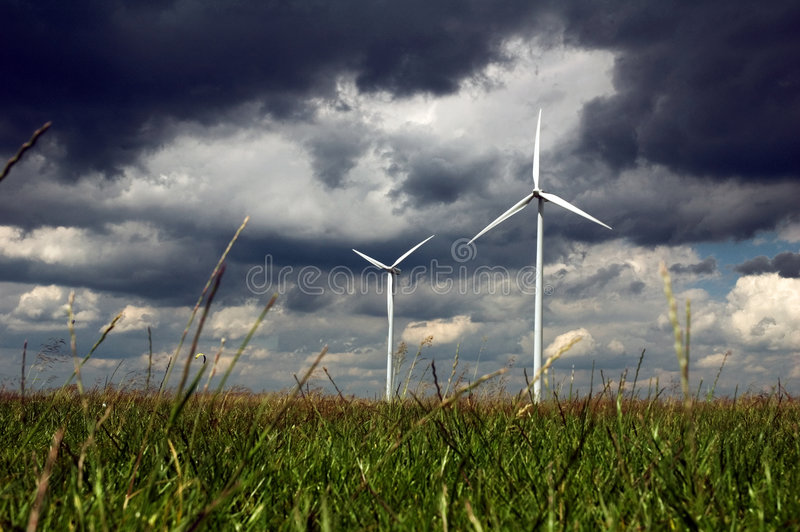 Windmill in green field stock photography