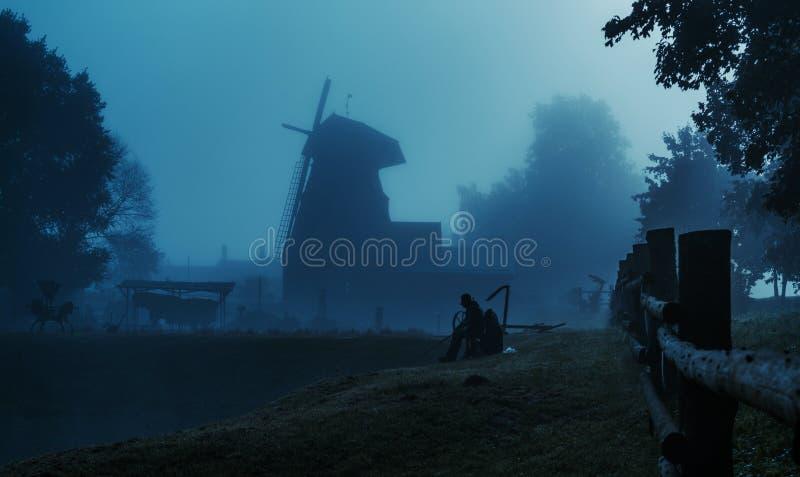 Windmill landscape, fisherman near pond at dusk hour royalty free stock image