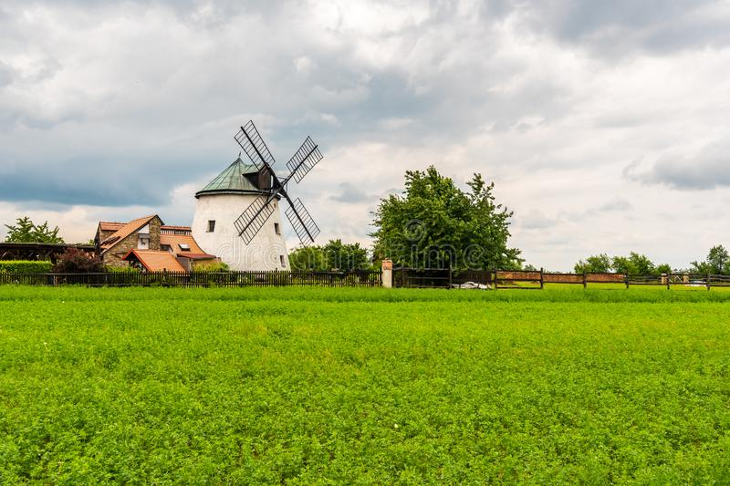 Windmill near the field with growing plant. Agriculture rural scene. Cloudy weather after rain, dramatic storm clouds.  stock photography