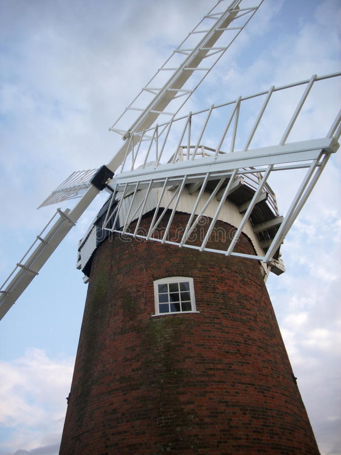 Windmill. From the near front with a background of blue sky with white clouds. Shows all four sails. Looking up at cap stock photo