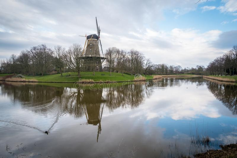 A windmill outside the city of Middelburg in the Netherlands. A beautiful sunset scene of a windmill on a canal from Middelburg, the Netherlands royalty free stock photo