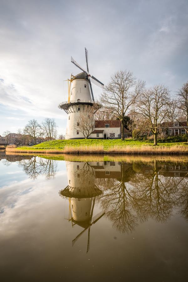 A windmill outside the city of Middelburg in the Netherlands. A beautiful sunset scene of a windmill on a canal from Middelburg, the Netherlands stock image