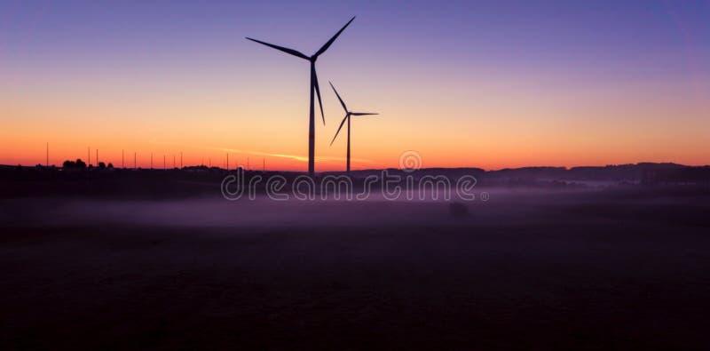 Windmill på solnedgången för lantgårdkälla för alternativ energi wind för turbiner royaltyfri fotografi