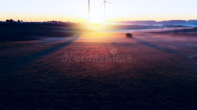 Windmill på solnedgången för lantgårdkälla för alternativ energi wind för turbiner royaltyfria foton