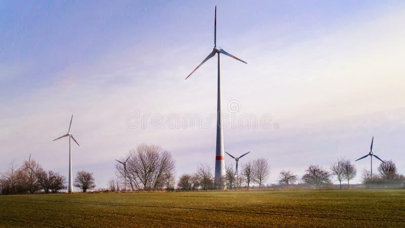 Windmill på solnedgången för lantgårdkälla för alternativ energi wind för turbiner royaltyfri foto