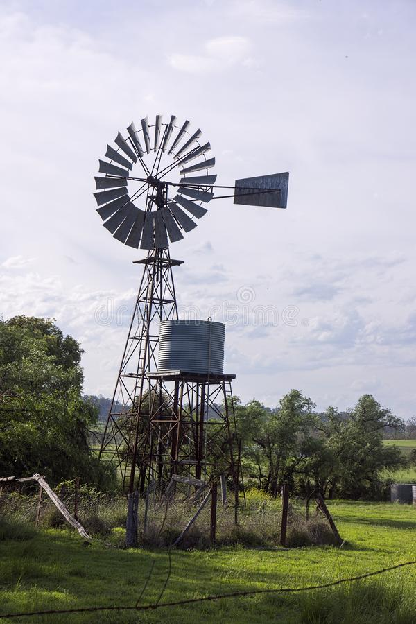Windmill pumping water into tank stock image