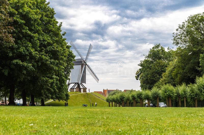 Windmill with People in Brugge. BRUGGE, BELGIUM - JULY 7, 2016 : Historical windmill on small hill in nature in Brugge, Belgium stock images