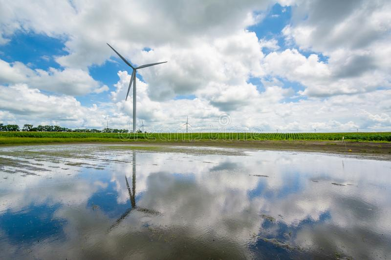 Windmill reflecting in a puddle in Rural Indiana.  stock photography