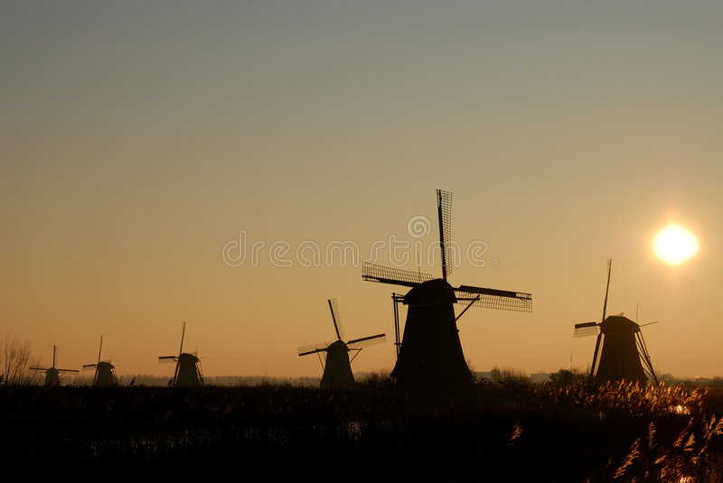 Windmill with rising sun. Netherlands, Kinderdijk, Drainage mill with rising sun royalty free stock photo