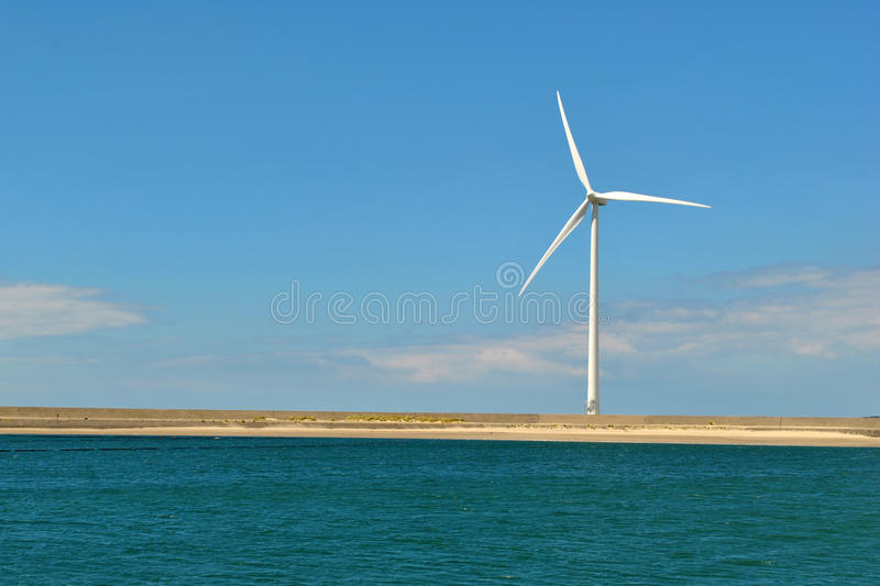 Windmill at sea - wind turbine. A wind turbine at sea in the Netherlands, used for green energy royalty free stock photography