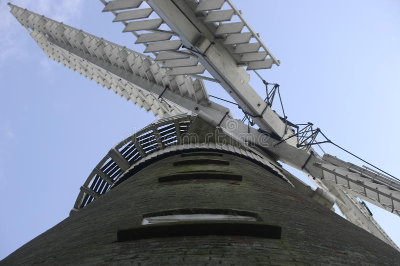 Windmill. Seen from below looking at the four sails on the cap up a row of windows. Background of blue sky royalty free stock photo