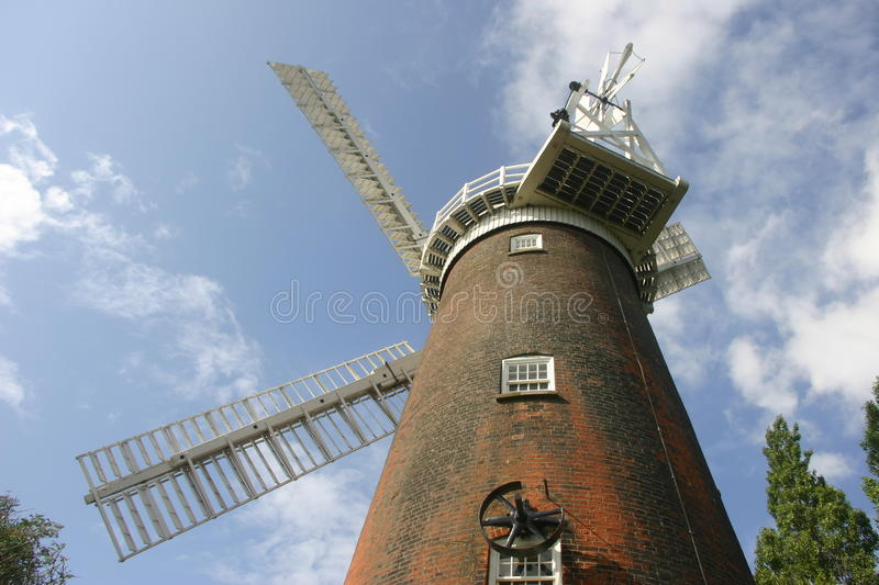 Windmill. Seen from below looking up at three sails with a background of blue sky with white clouds and trees stock photography