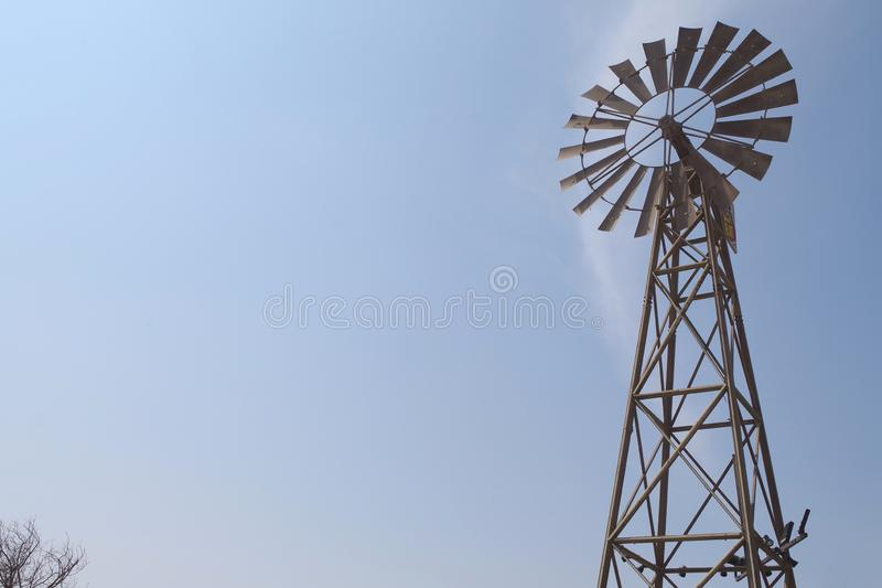 An old Windmill silhouette with bright and blue sky. Beautiful american countryside icon. A Windmill silhouette with bright and blue sky. Beautiful american royalty free stock images