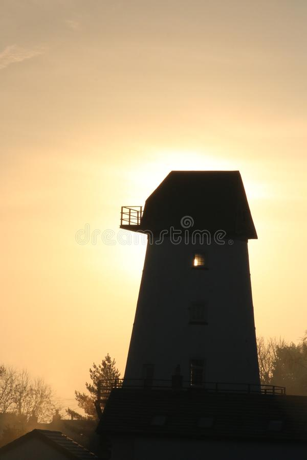 Windmill silhouette at sunrise stock photography