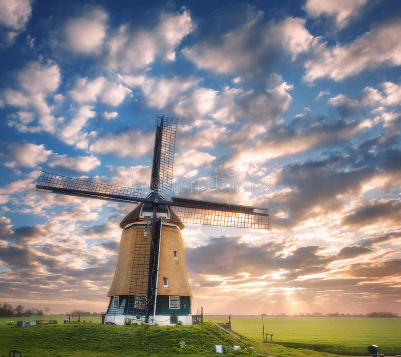 Windmill at sunrise in Netherlands. Beautiful old dutch windmill. Against colorful sky with clouds. Spring landscape in the morning in Holland. Rural scene stock photo