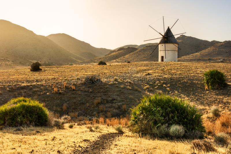 Windmill at sunset between the hills. Light and golden fields in southern Spain. stock images