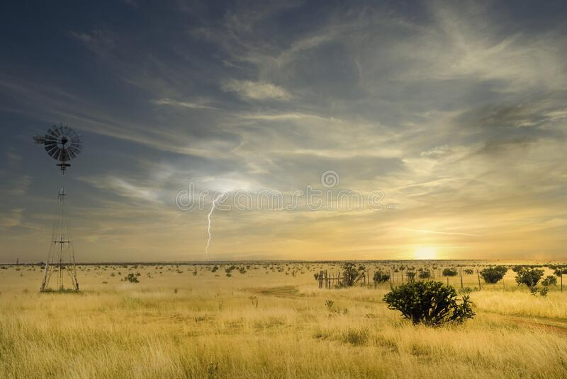 Windmill in a Texas field along Route 66 with a storm approaching stock images
