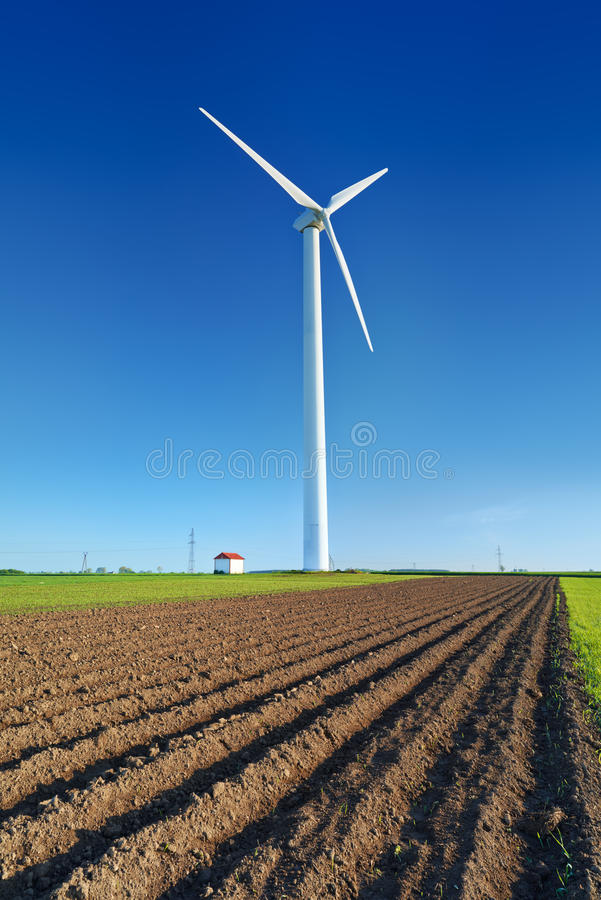 Windmill turbine on blue sky. Wind energy. Modern green power. royalty free stock photo