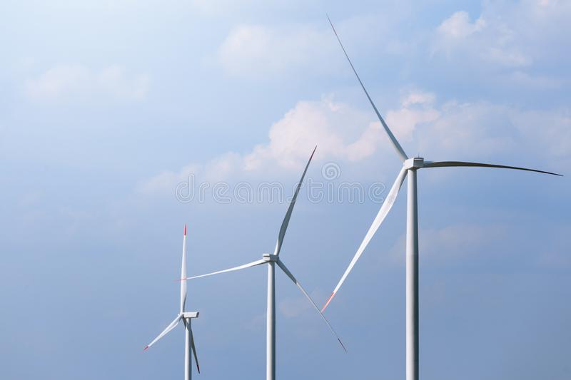 Windmill turbine farm with partly cloudy blue sky in background. Renewable energy wind turbines royalty free stock photography