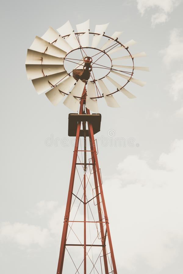 Windmill in vertical format using desaturated tones. Windmill in a blue sky. With a little retouch of faded tones. Renewable energy. Power of wind. Planet care royalty free stock photos