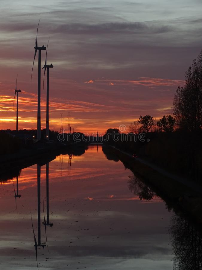 Windmills at canal at sunset. With reflections in the water and trees beside royalty free stock photography