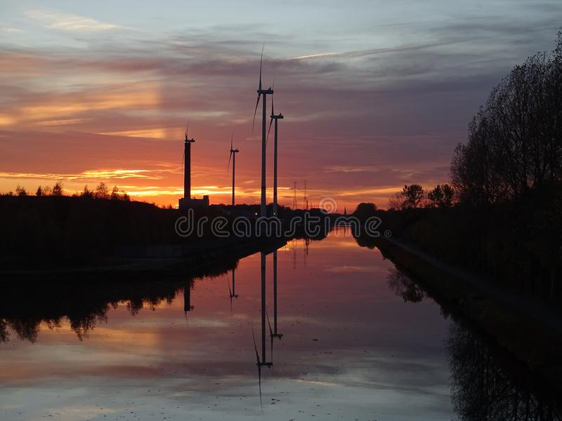 Windmills at canal at sunset. With reflections in the water and trees beside royalty free stock photos