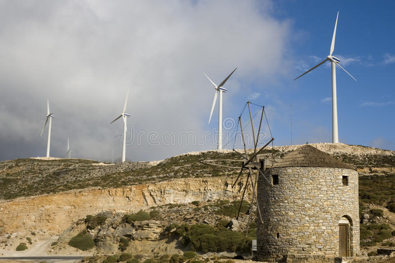 Windmills - contrast old and new. Old windmill lower new wind power - Naxos island Greece royalty free stock image