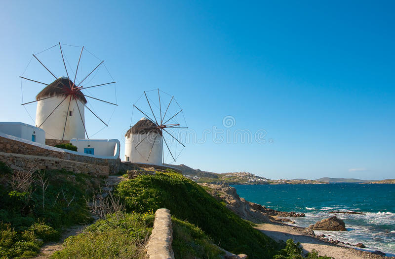 Windmills on a green hillside near the sea. A visiting card of Mykonos Island royalty free stock photography