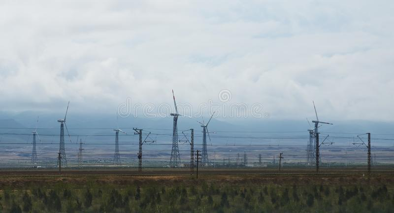 Windmills and high-voltage electrical towers along the road. With green hills and gloomy sky in the background royalty free stock photos