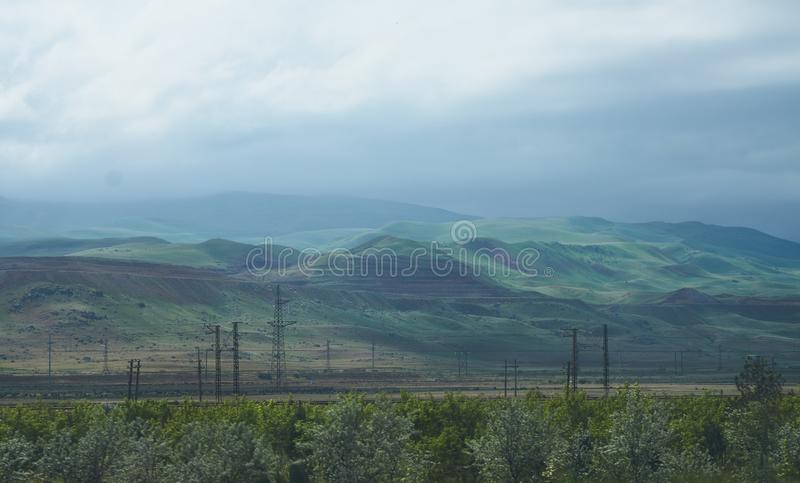 Windmills and high-voltage electrical towers along the road. With green hills and gloomy sky in the background stock photo