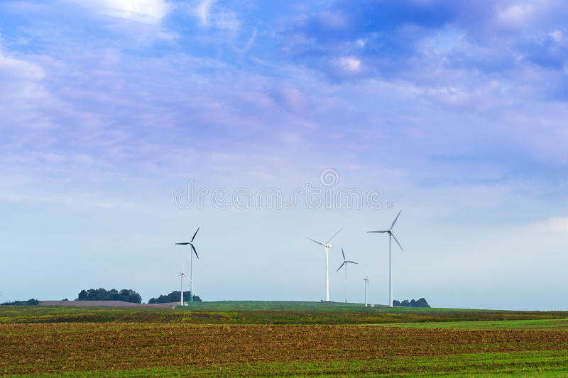 Windmills rotate blades over farmland. Windmills rotate blades over arable fields and farmland. Electric wind generators produce environmentally clean stock images
