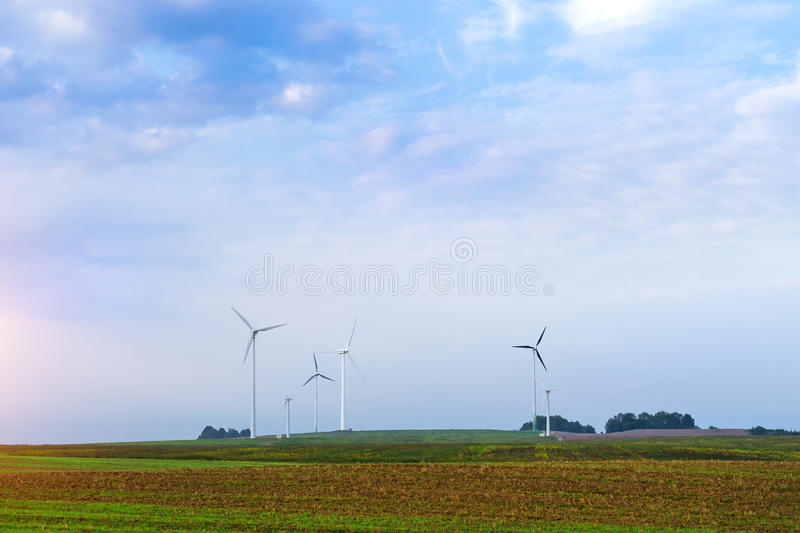 Windmills rotate blades over farmland. Windmills rotate blades over arable fields and farmland. Electric wind generators produce environmentally clean royalty free stock images