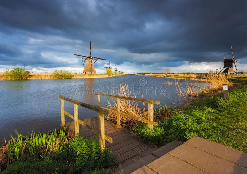 Windmills at sunset in Kinderdijk, Netherlands. Rustic landscape. With wooden pier against traditional dutch windmills near the canals and cloudy blue sky stock photography